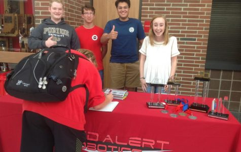 A student signs up for Red Alert Robotics with seniors Josh Stevenson, Kevin Beshears, Chase Rivas and Meredith Fain.