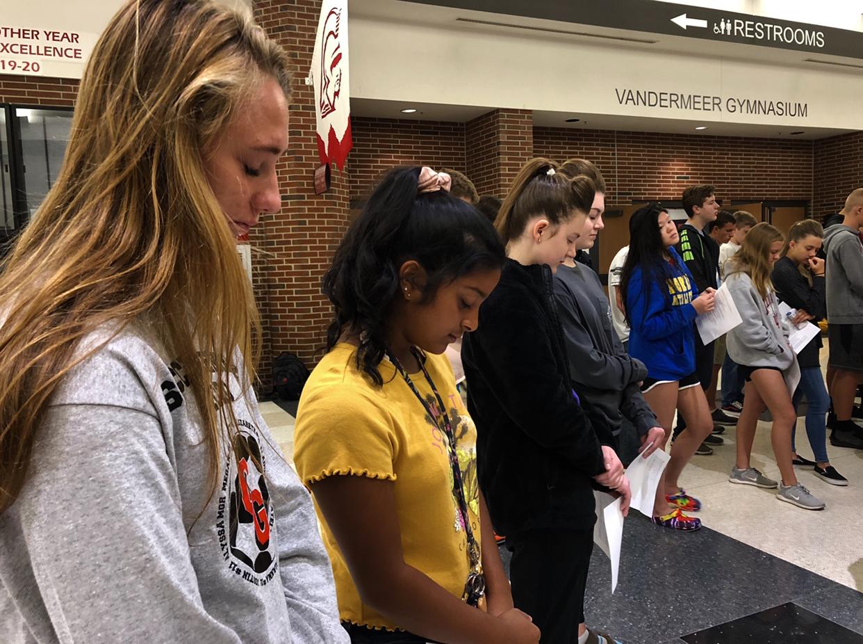 Seniors Katelyn Jansen and Leanna Sequeira pray with student leader