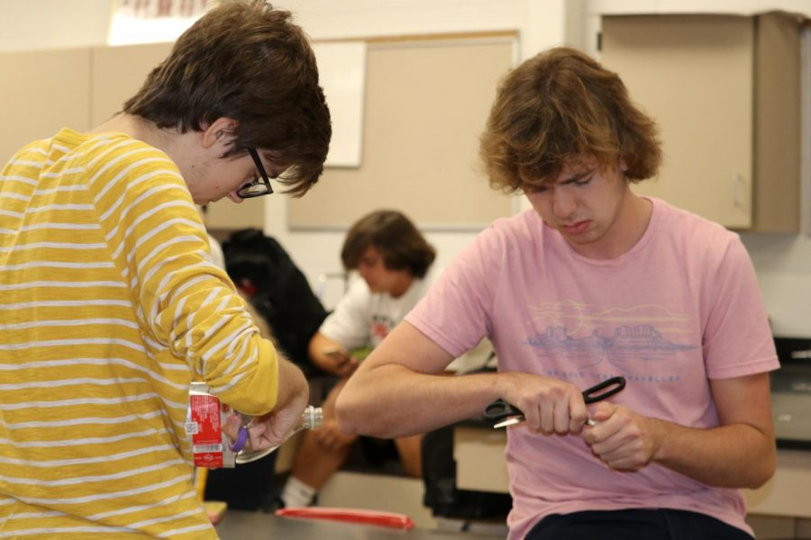 Seniors Ian Kelly and Jonathan Jeffries make one of the 2-liter bottle planters.