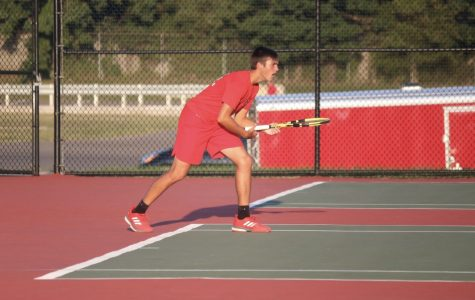 Junior Carson Contos looks to return a shot against his opponent.