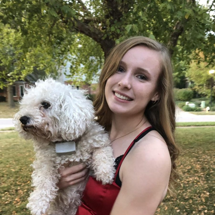 Senior Kelsey Osborne poses for a picture with a friends dog, Mya, before Homecoming 2019.