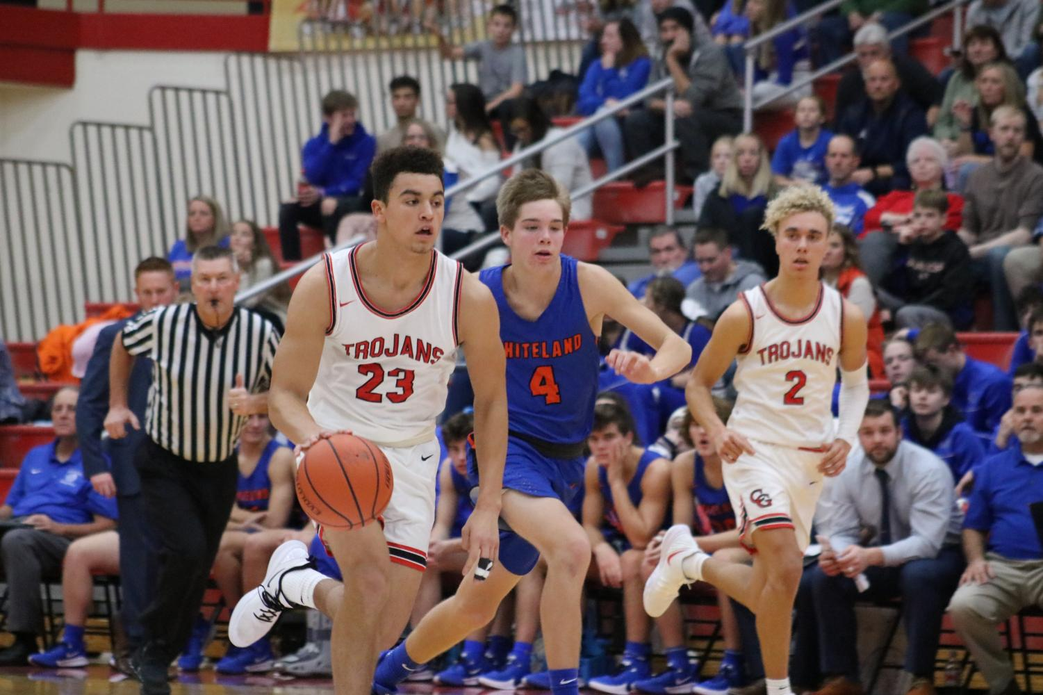 Junior Leyton Mcgovern dribbles the ball down the court during the Trojans' second match against Whiteland, followed closely by sophomore Tayven Jackson.