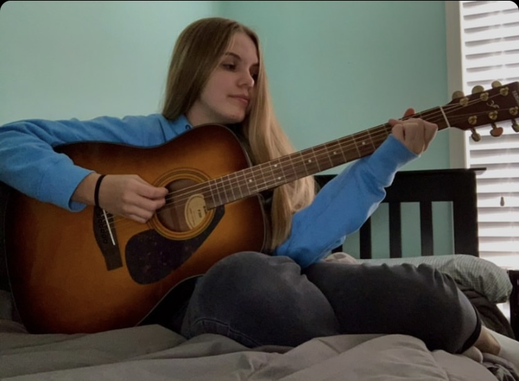 Sophomore Taylor McLaughlin strums her guitar as she writes song.
