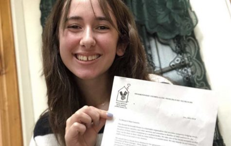 Senior Olivia Medina poses with a letter from the Ronald McDonald House, where she volunteers.