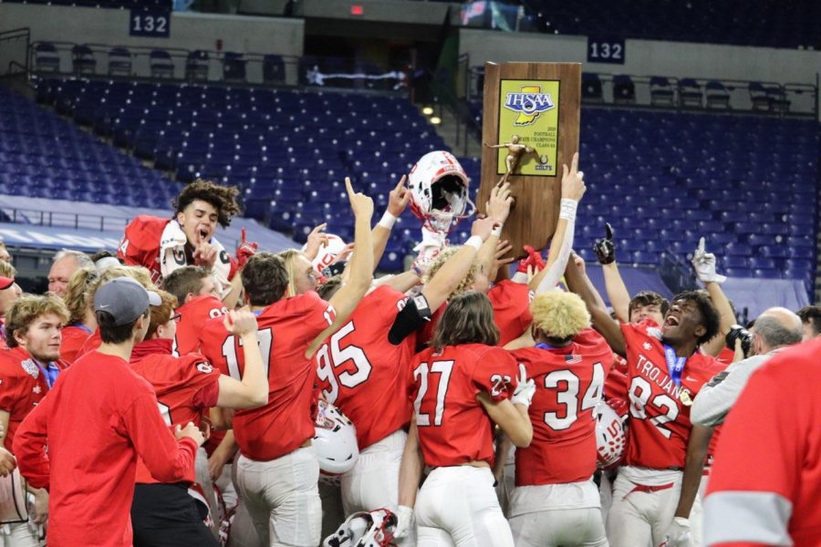 The Trojans hold up their  state championship trophy, with the empty bleachers of Lucas Oil Stadium behind them.