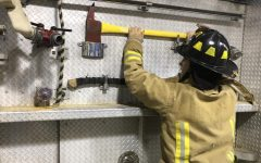 Junior Alex Riley grabs a firefighting axe off the truck.