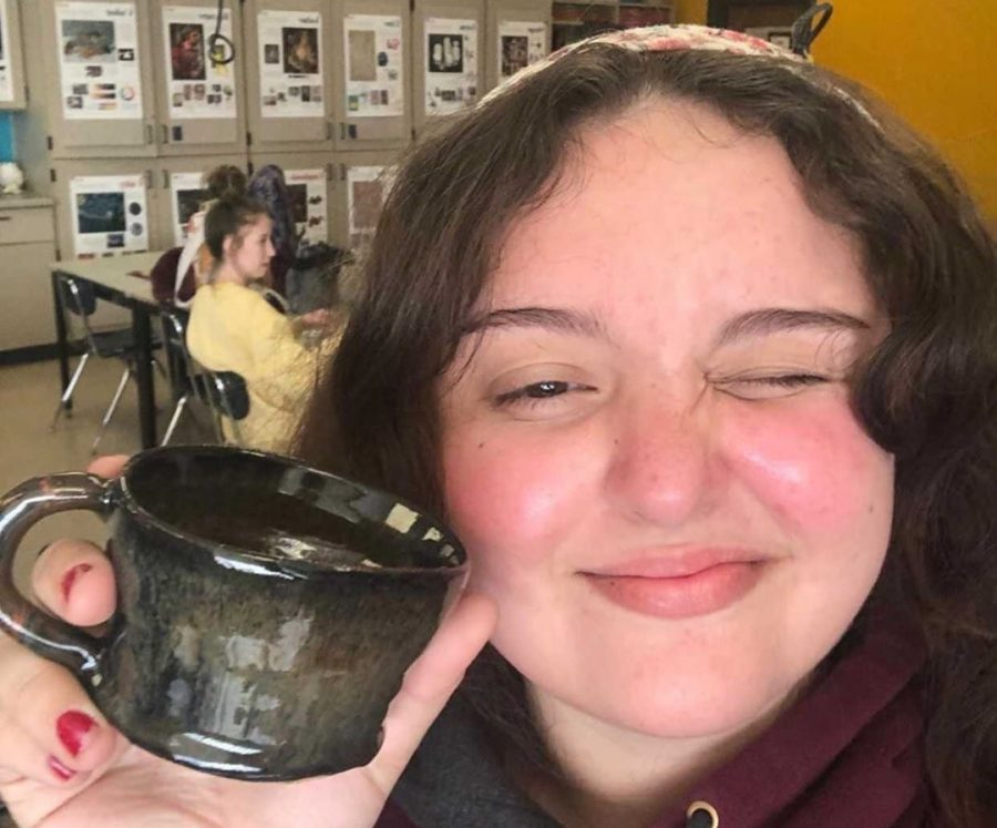 Virginia Foust '21 holds up a self-made mug in one of her art classes.