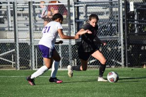 Junior Emily Karr dribbles the ball past a defender during the teams 9-0 win against Ben Davis.